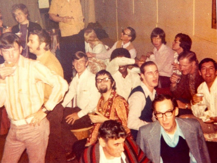 A photograph of about 15 patrons of the Up Stairs lounge. Some are sitting at tables holding cocktails; others are posing by holding a hand on a cocked hip. They are all men.
