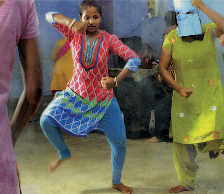 A scene from the documentary Little Stones that shows three girls stomping and dancing.