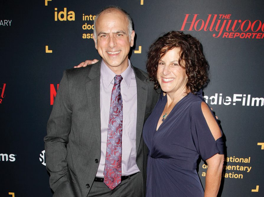 Jody Becker, wearing a blue formal dress, stands with Dan Habib, who's wearing a suit and a tie, in front of a black screen that has the names of different film organizations, such as International Documentary Association, and film publications, such as Hollywood Reporter, written in different colors and fonts across the screen.