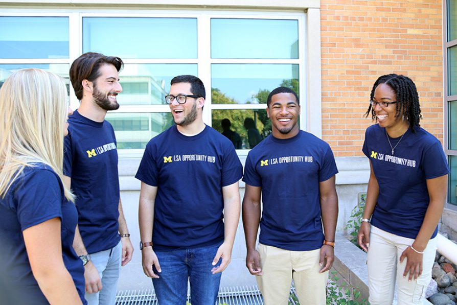 Students in Opportunity Hub t-shirts laughing and talking together