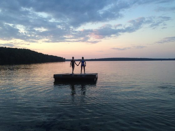 Two young women are show on a diving platform on an inland lake at sunset, with a sky of pinks and blues.