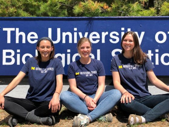 Erin Zettell, Natalie Manitius, and Amanda Lownes sit cross-legged in front of the UMBS sign