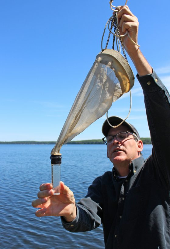A man holds up a plankton tow, which comprises a cone-shaped net with a small glass bottle on the end.