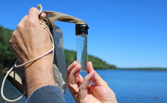 A pair of hands holds a small glass jar filled with lake water. In the background, a treed shoreline is visible.